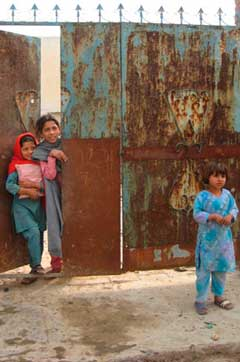 Children at the metal door of a home